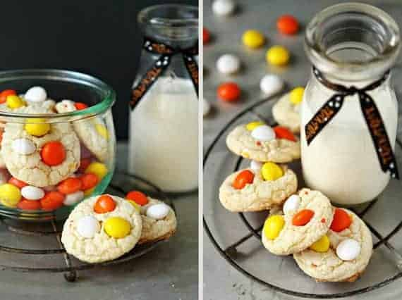Cake mix cookies with candy corn m&m's on a round cooling rack next to a glass of milk