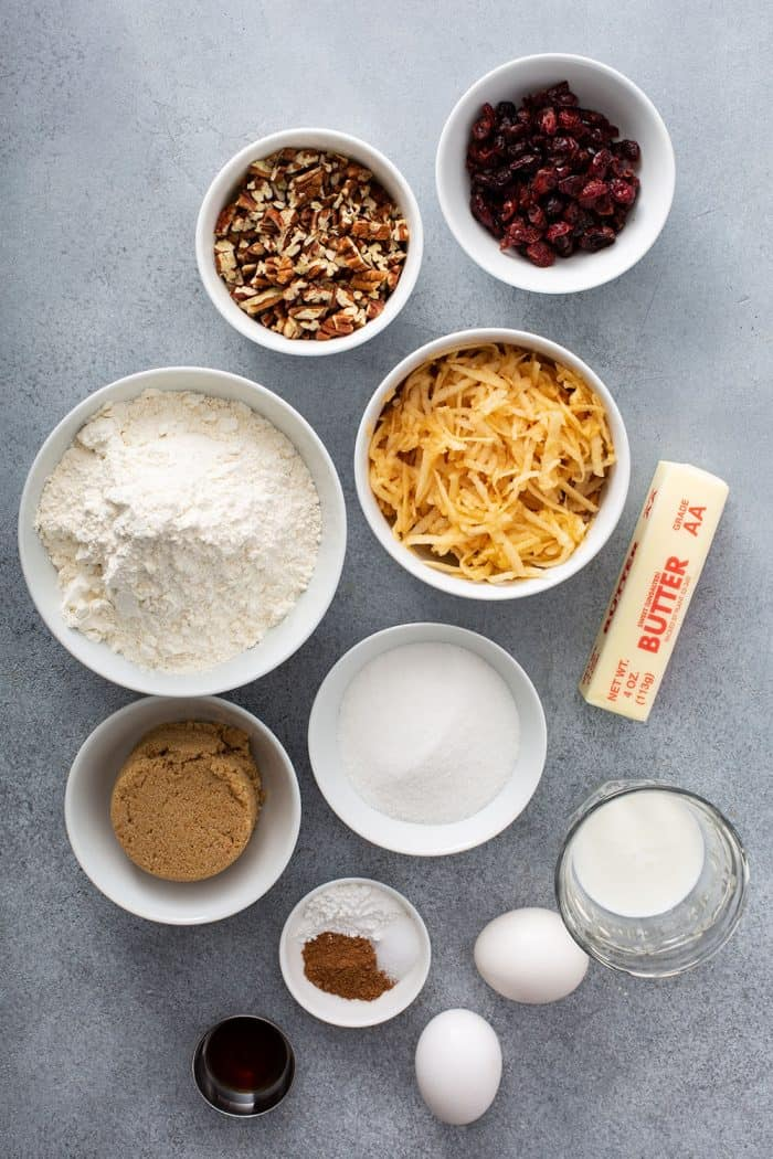 Overhead view of the ingredients for apple pie bread arranged in bowls on a gray countertop