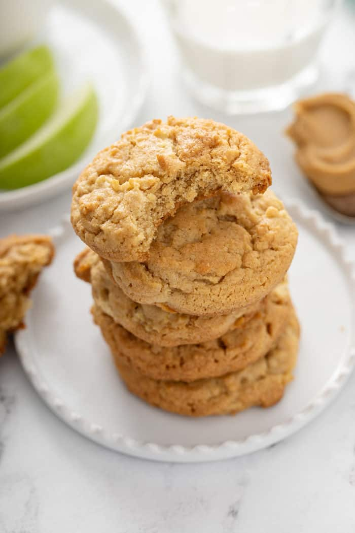 5 apple peanut butter cookies stacked on a white plate. The top cookie has a bite taken out of it