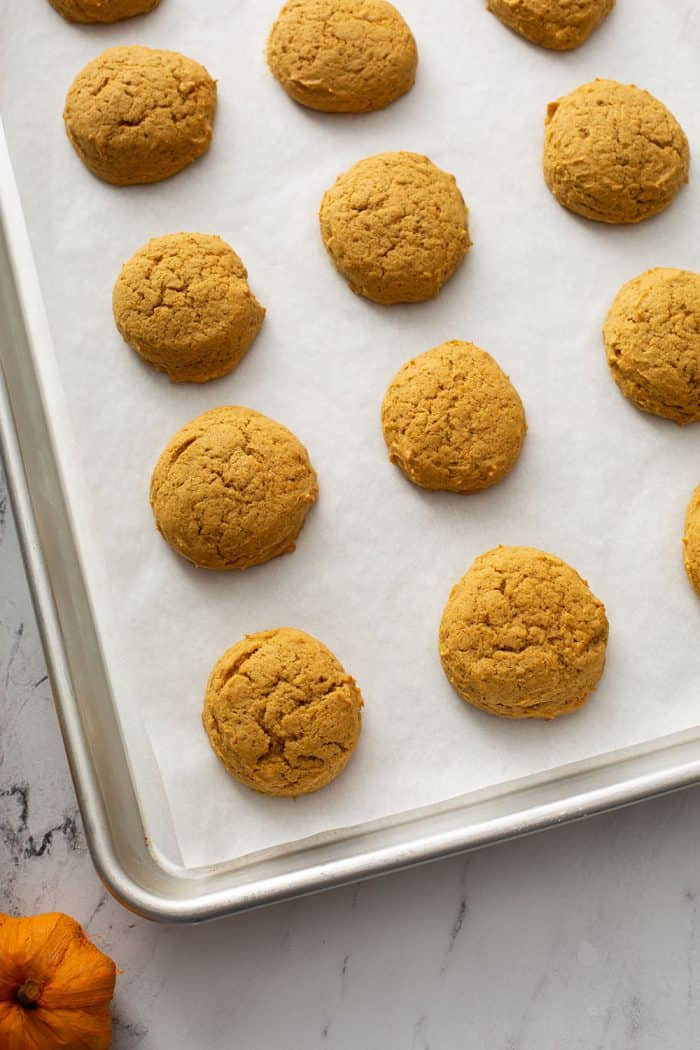 Baked pumpkin cookies on a parchment-lined cookie sheet