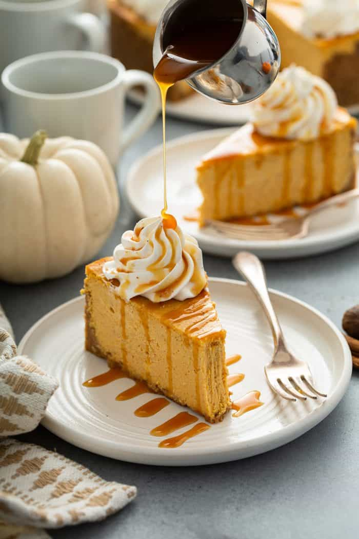 Caramel sauce being drizzled over a slice of pumpkin cheesecake