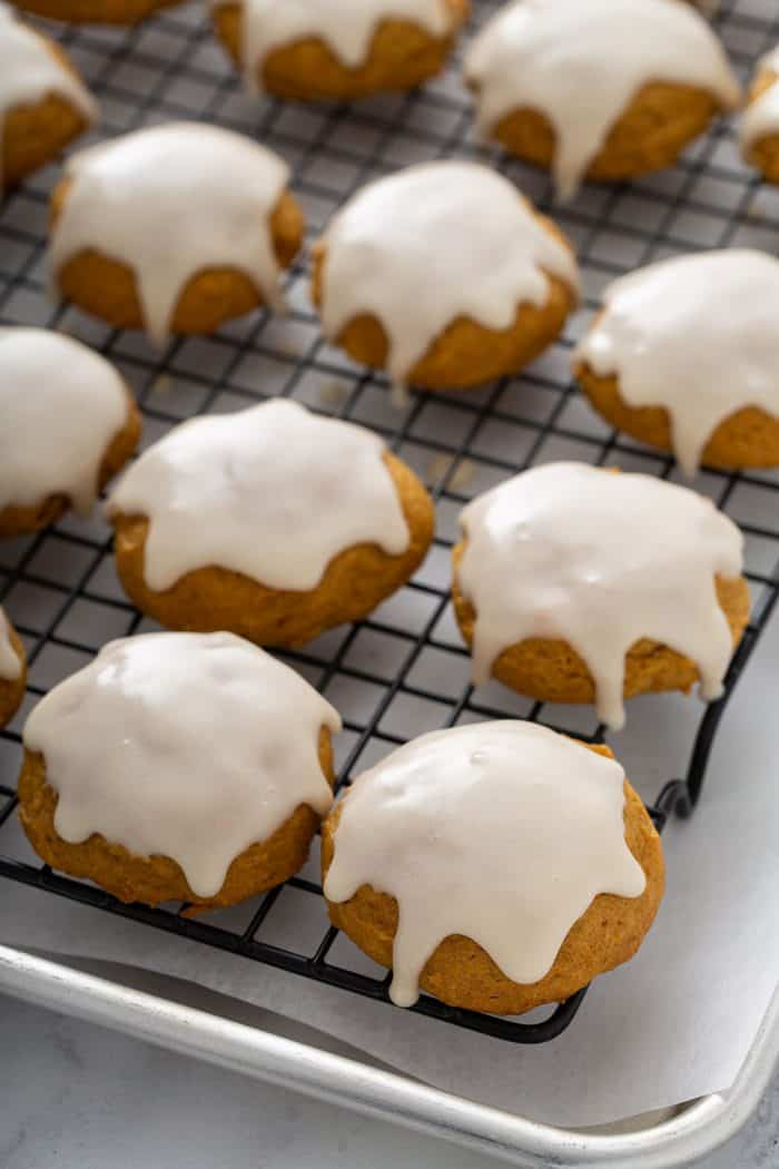 Iced pumpkin cookies lined on a cooling rack