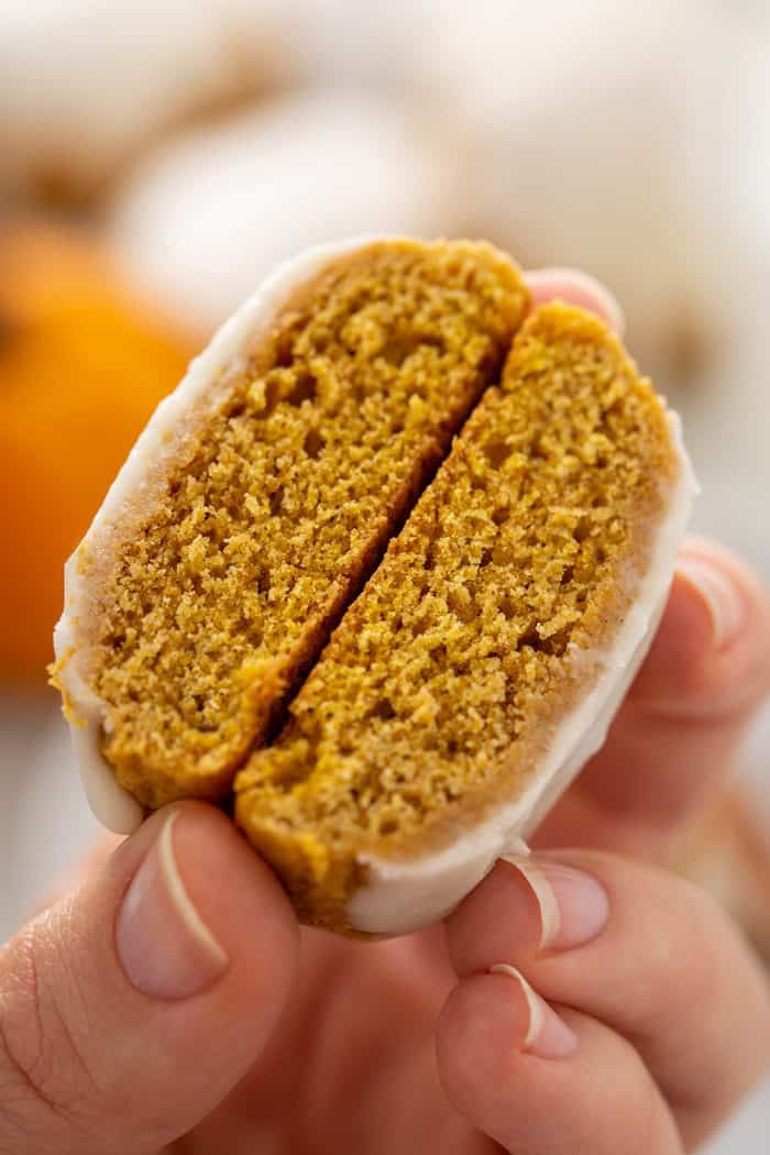 Hand holding a cut-open pumpkin cookie to show the texture inside