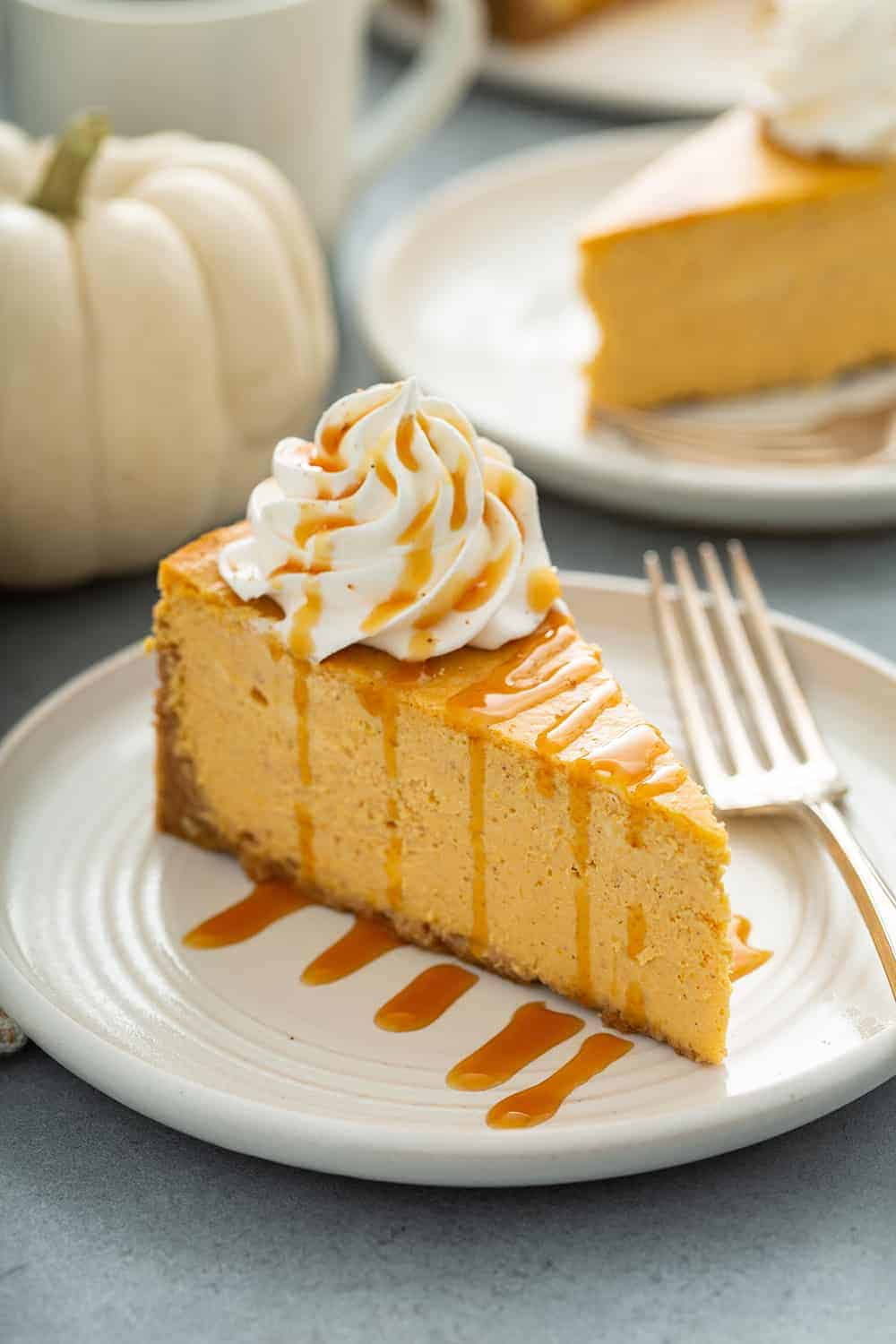 Slice of pumpkin cheesecake next to a fork on a plate