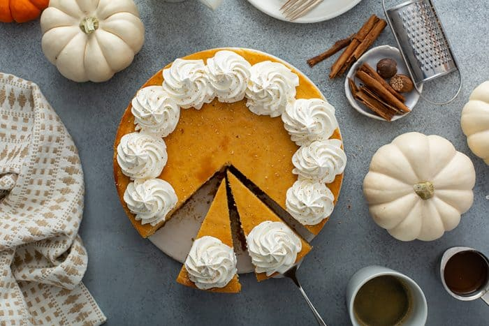 Overhead view of a sliced pumpkin cheesecake topped with whipped cream