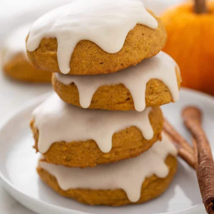Four iced pumpkin cookies stacked on a white plate