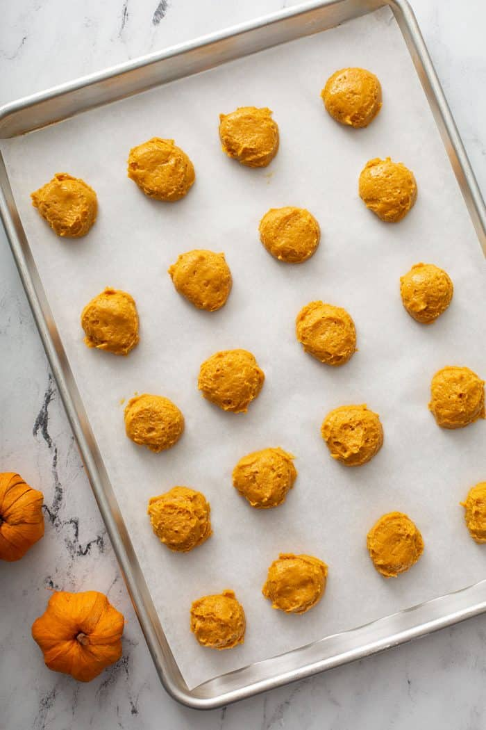 Pumpkin cookie dough portioned onto a parchment-lined cookie sheet