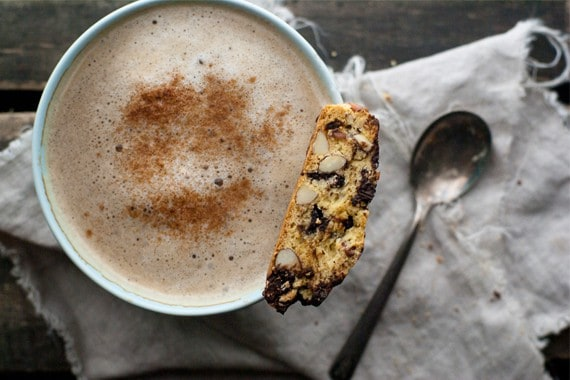 A chocolate cherry almond biscotti sitting on a mug of cappuccino