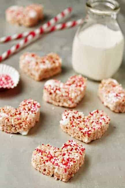 Heart shaped rice krispie treats with red and white sprinkles on top