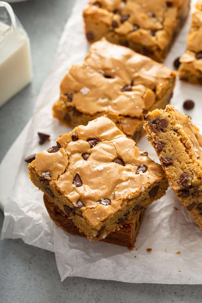 Stacked chocolate chip blondies on a piece of parchment paper