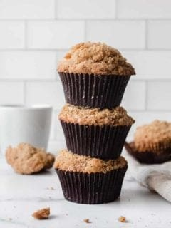 Three banana crumb muffins stacked on top of each other on a marble countertop