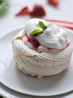A meringue next on a round plate next to a fork