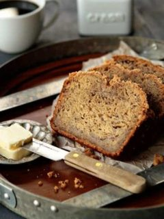 Sliced banana bread on a serving tray next to butter and a knife