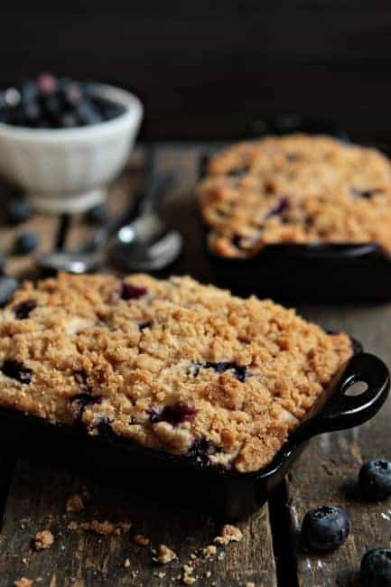 Blueberry buckle in a black baking dish on a wood surface