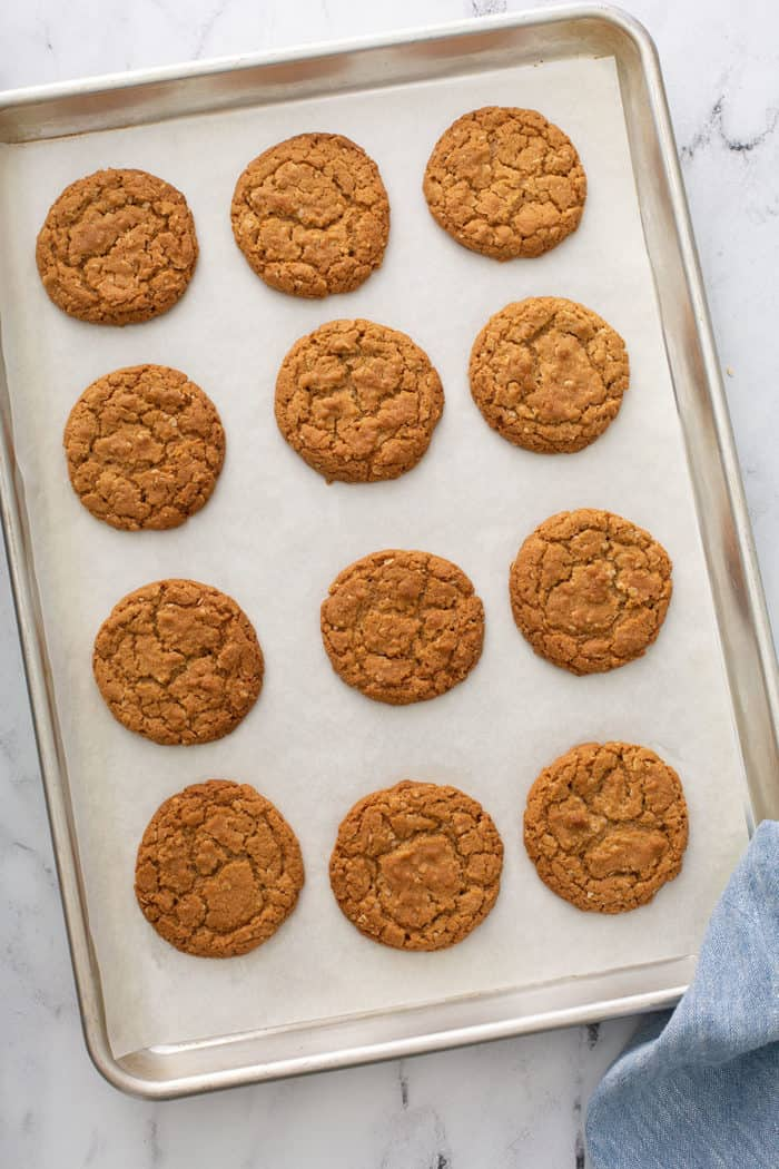 Baked biscoff cookies cooling on a parchment-lined sheet pan