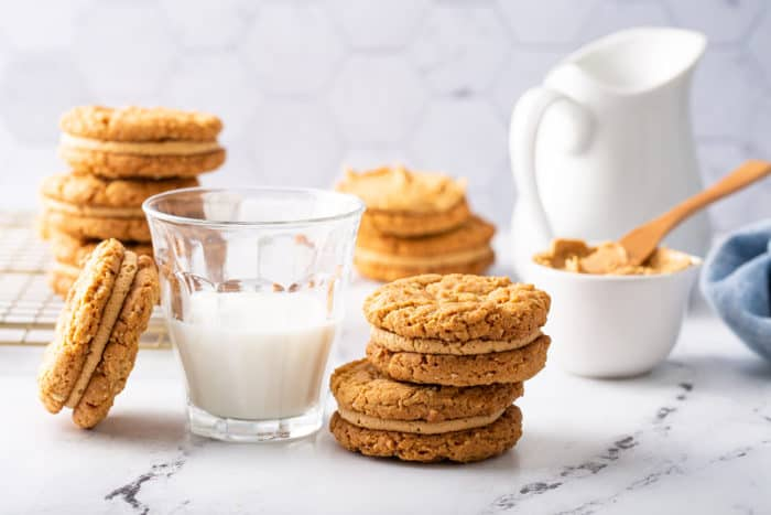 Biscoff sandwich cookies stacked next to a glass of milk on a marble counter