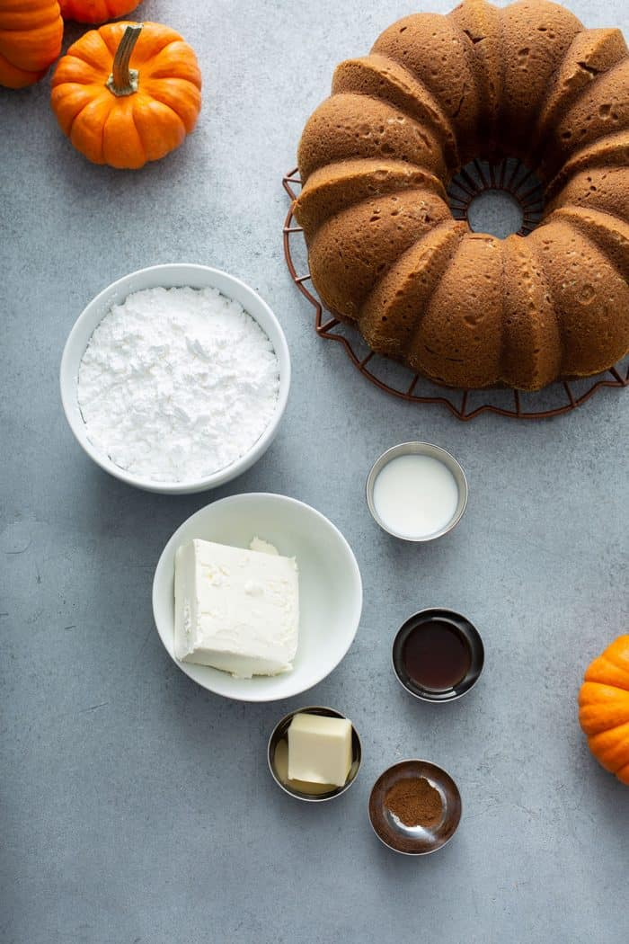 Cream cheese frosting ingredients next to a pumpkin bundt cake on a gray counter