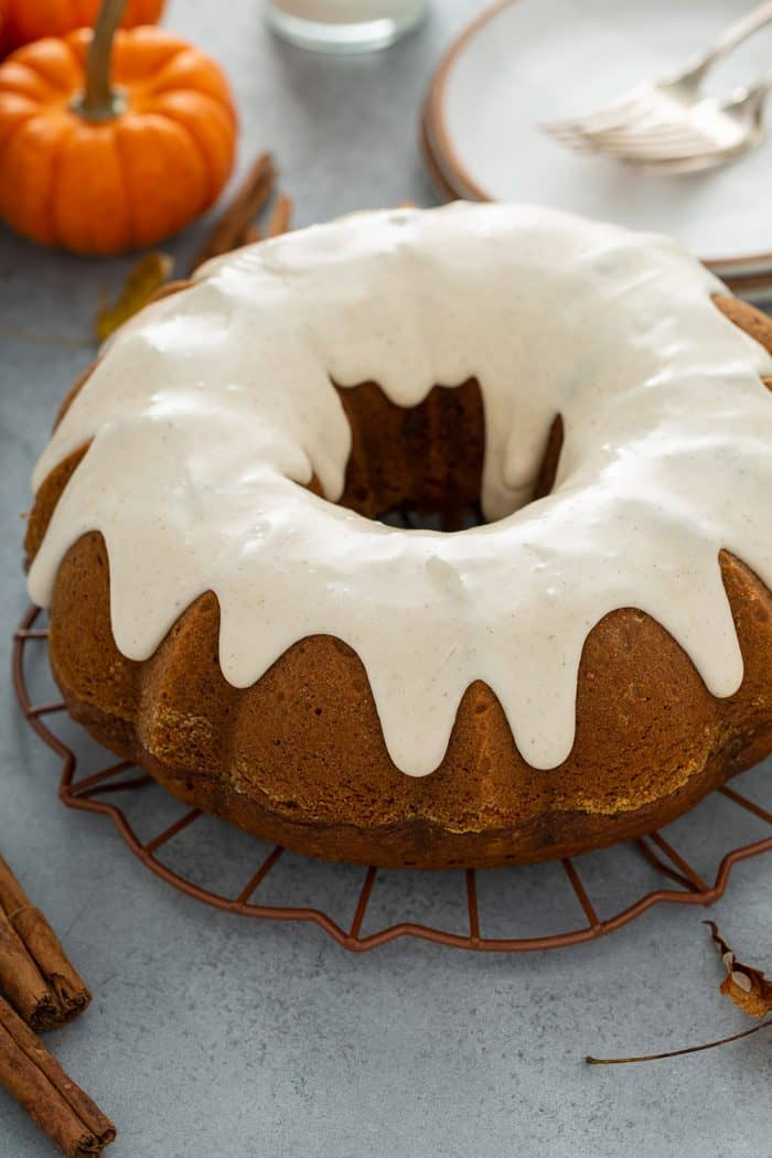Frosted pumpkin bundt cake on a wire rack