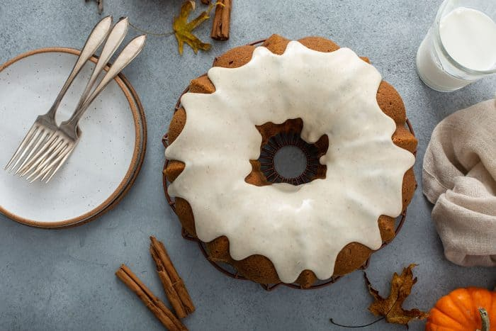 Overhead view of a frosted pumpkin bundt cake next to white plates and forks for serving