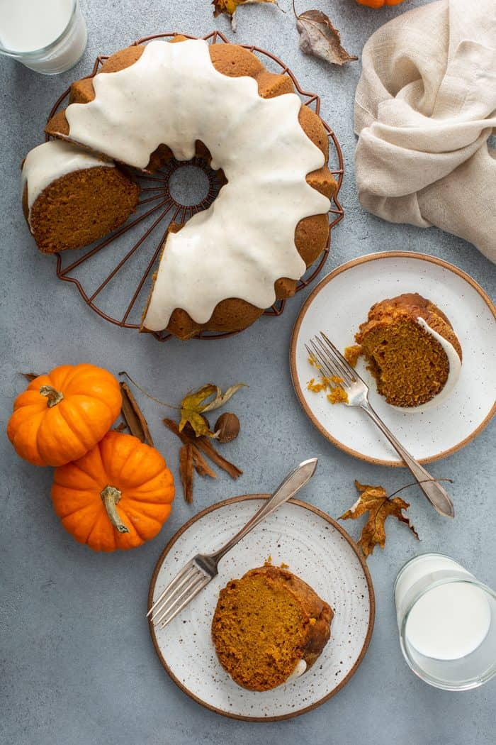 Overhead view of a sliced pumpkin bundt cake next to two white plates with slices of cake and forks on them
