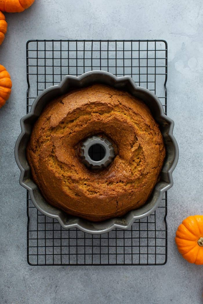Baked pumpkin cake in a bundt pan on a wire rack