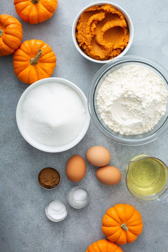 Ingredients for pumpkin bundt cake arranged on a gray counter