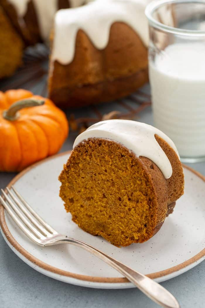 Slice of pumpkin bundt cake next to a fork on a white plate