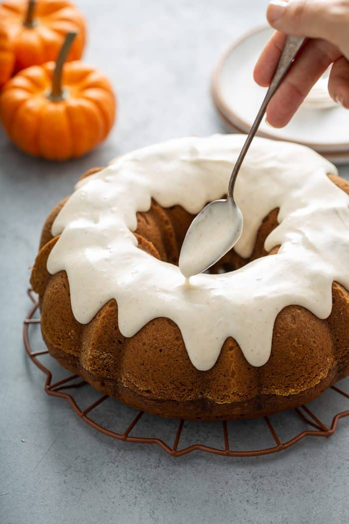 Spoon drizzling cream cheese frosting onto a pumpkin bundt cake