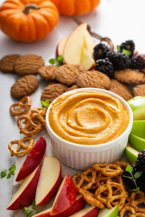 Pumpkin dip in a white bowl surrounded by fruit, pretzels, and cookies
