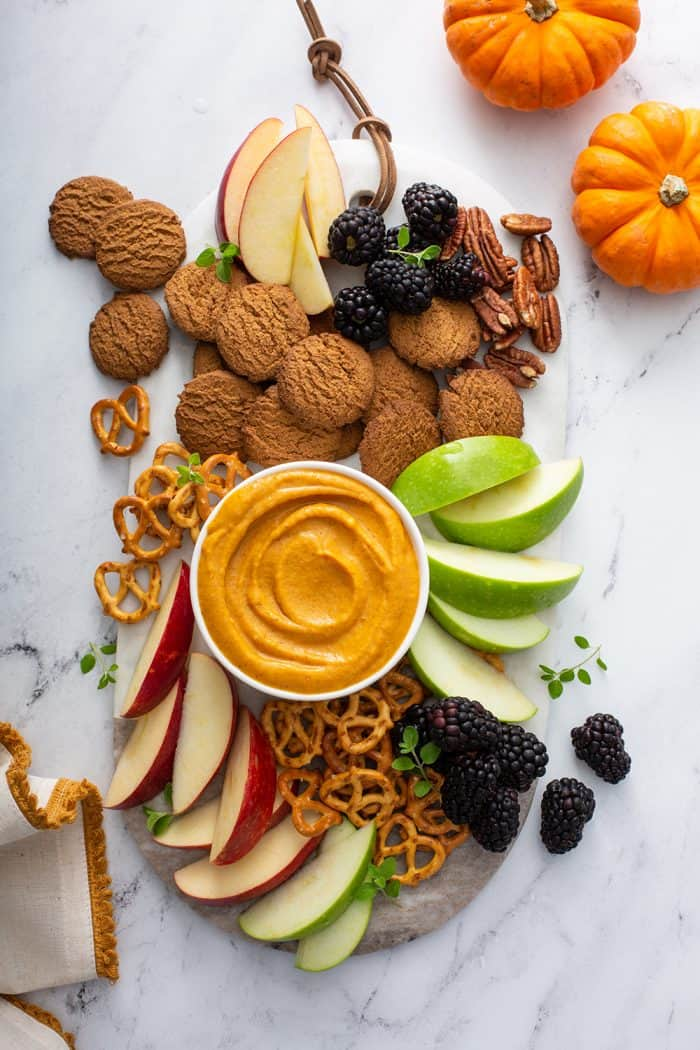 Bowl of pumpkin dip on a board surrounded by fruit, cookies, and pretzels