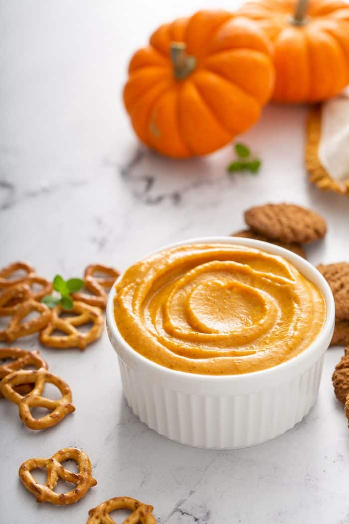 Bowl of pumpkin dip on a marble counter surrounded by pretzels
