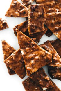 Shards of pecan brittle on a piece of parchment paper