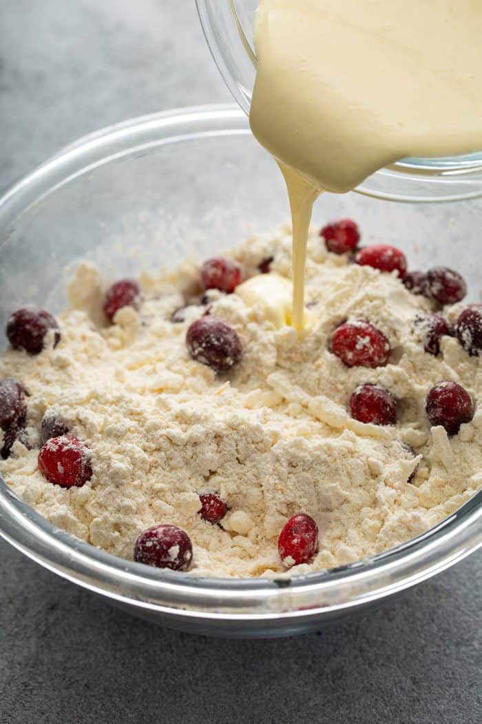 Wet ingredients being poured into a glass mixing bowl holding the dry ingredients for cranberry scones