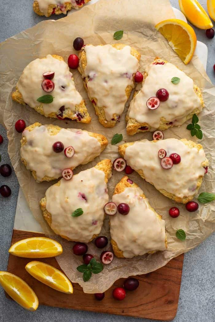 8 glazed cranberry orange scones arranged in a circle on a piece of parchment