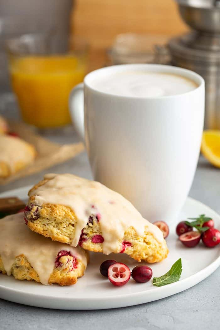 Cranberry orange scones on a white plate next to a mug of coffee