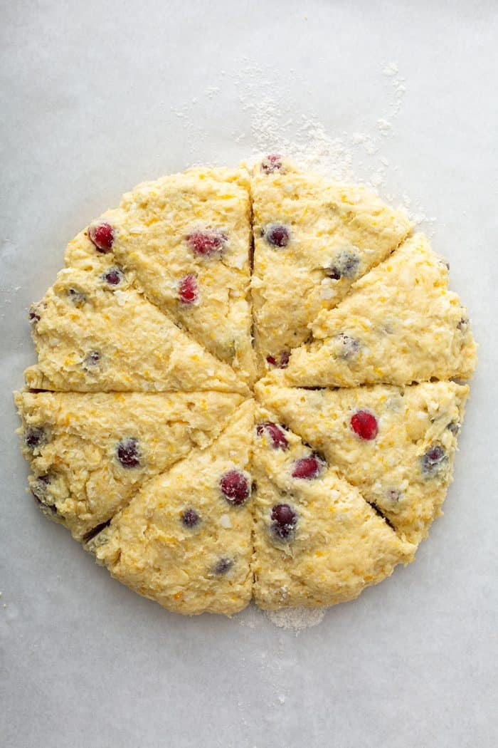 Cranberry scone dough shaped into a circle and cut into 8 pieces on a floured surface