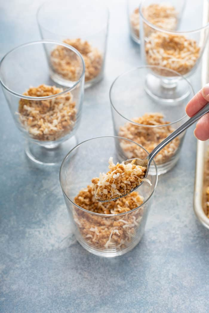 Spoon portioning graham cracker crumble into individual glass dishes