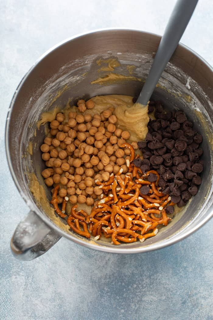 Caramel bits, chocolate chips, and pretzels being added to blondie batter in a metal mixing bowl