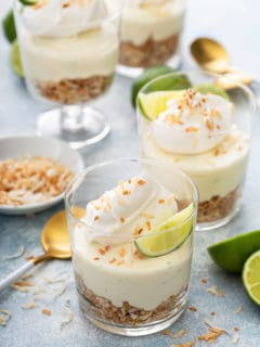 Assembled key lime cheesecakes topped with whipped cream and lime wedges
