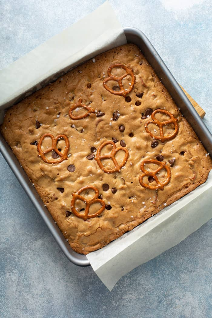 Baked salted caramel blondies with pretzels in a metal baking pan