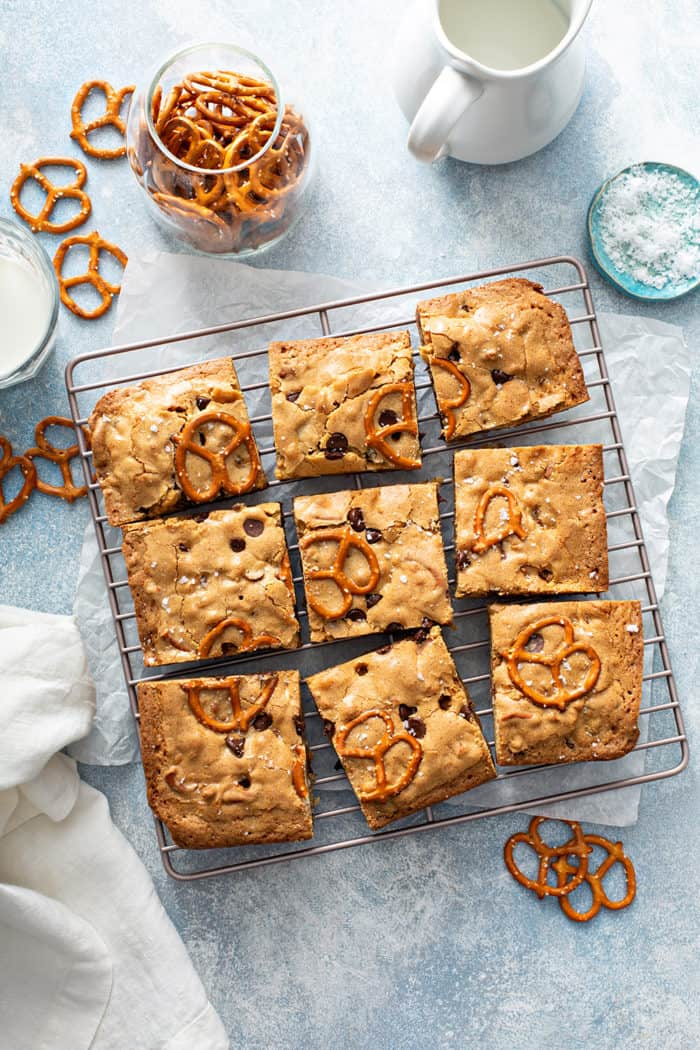 Overhead view of sliced salted caramel blondies with pretzels on a metal cooling rack