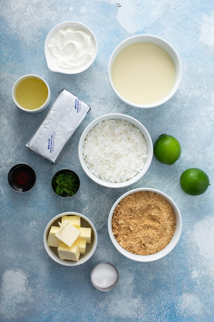 Ingredients for key lime cheesecakes on a blue countertop