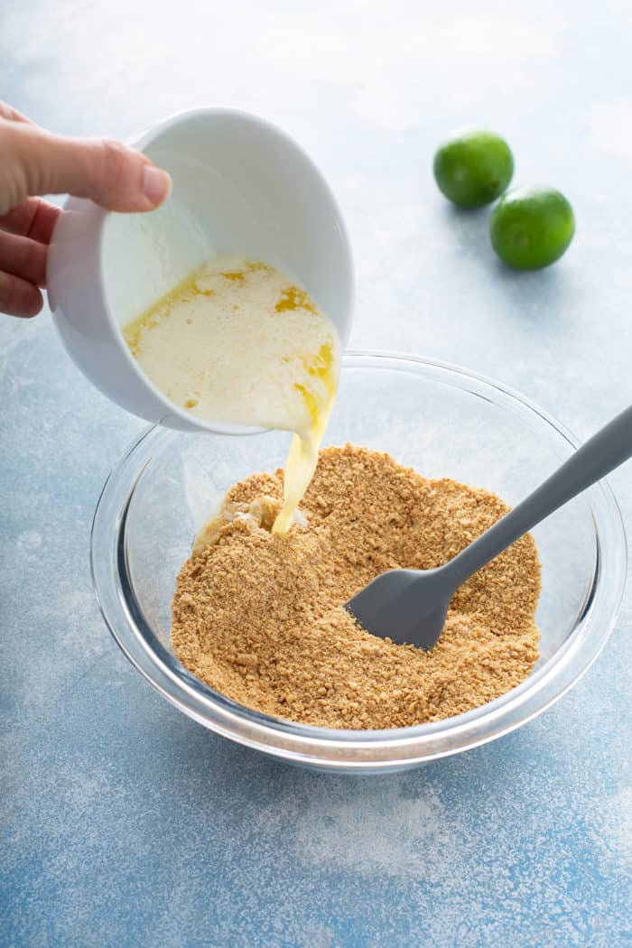 Spatula stirring together graham cracker crust crumble for key lime cheesecakes