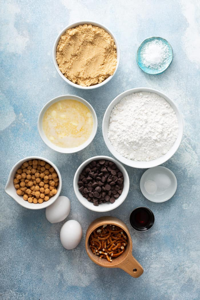 Ingredients for salted caramel blondies with pretzels on a blue countertop