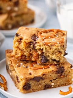 Two salted caramel blondies with pretzels stacked on a white plate