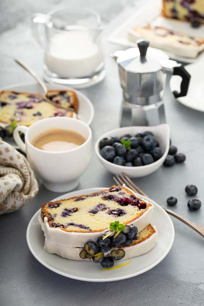 Slices of lemon blueberry bread on a white plate with cups of coffee, a bowl of blueberries, and a second plate of bread in the background