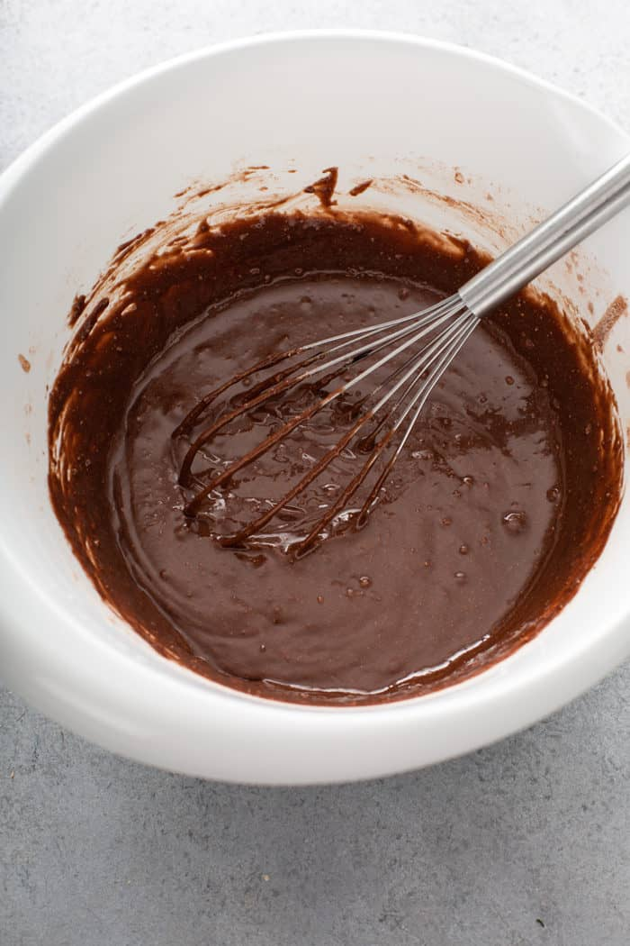 Whisk stirring batter for salted caramel brownies in a white mixing bowl