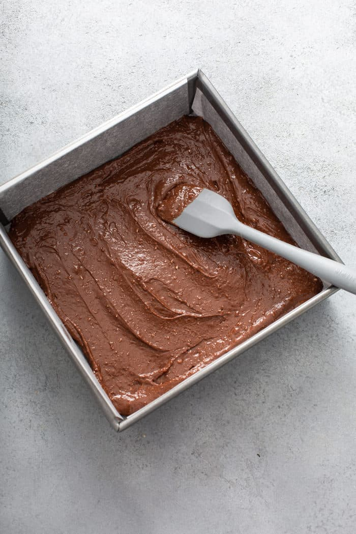 Spatula spreading salted caramel brownie batter into a metal baking pan