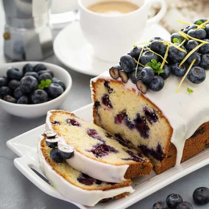 Sliced loaf of lemon blueberry bread topped with fresh blueberries on a white platter