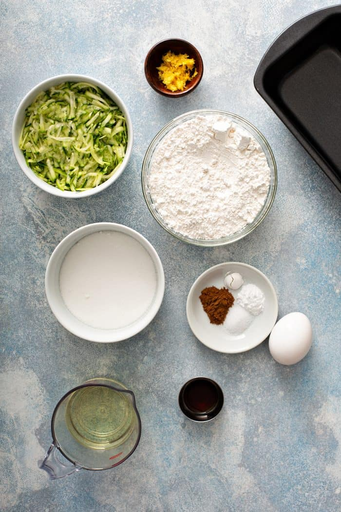 Overhead view of an assortment of bowls holding the ingredients for lemon zucchini bread